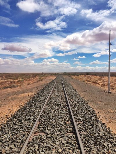 Surface level of railroad track against cloudy sky
