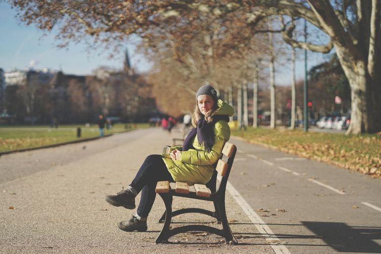 Full length portrait of man sitting on seat in park