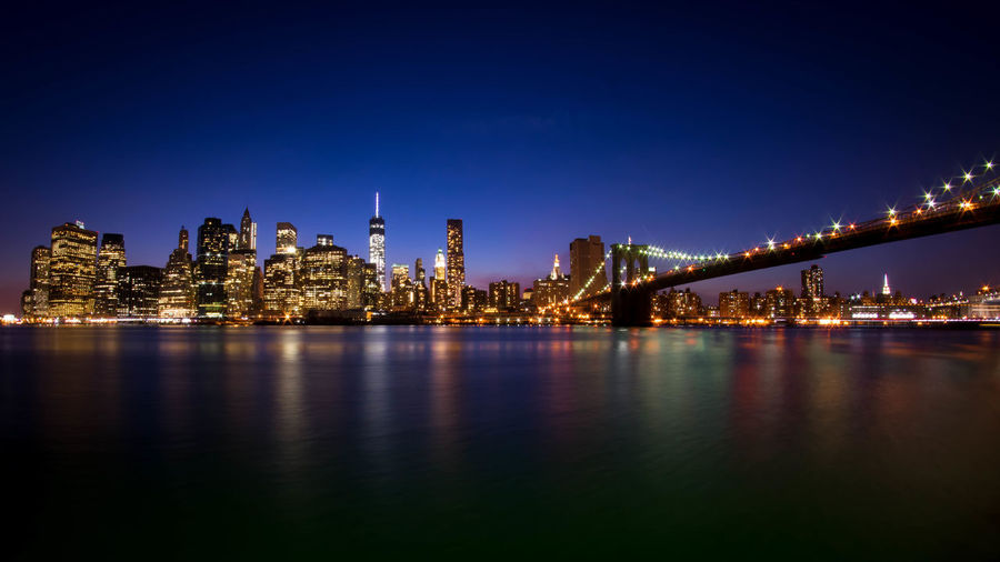 Low angle view of brooklyn bridge over east river in illuminated city