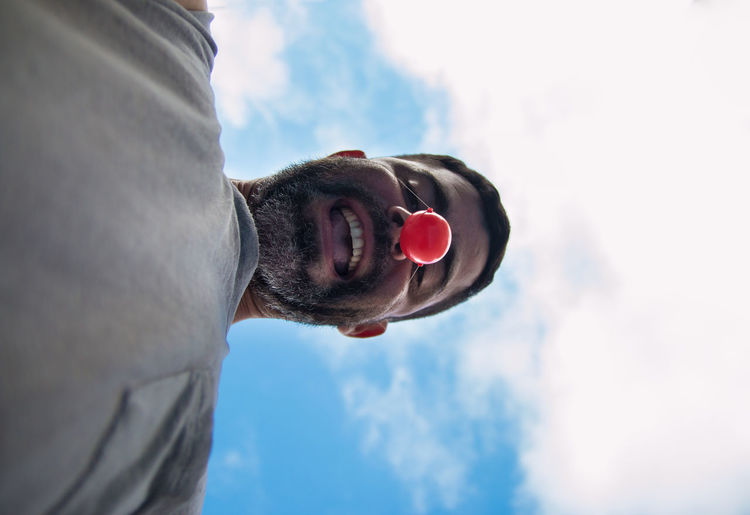 Low angle portrait of man wearing clown nose against cloudy sky