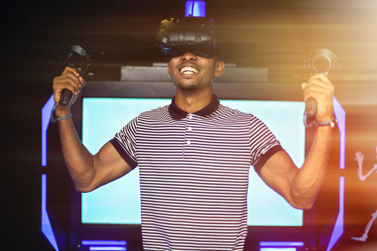 Virtual Reality Simulator Virtual Reality Gaming One Person Front View Happiness Smiling Real People Standing Indoors  Young Men Young Adult Emotion Striped Men Casual Clothing Holding Focus On Foreground Lifestyles Technology Portrait Waist Up