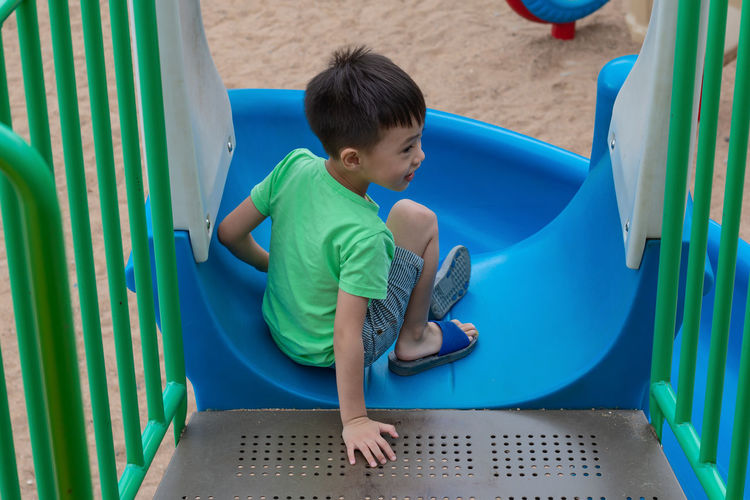 High angle view of boy sitting on slide in playground