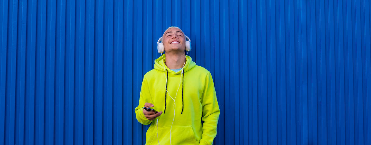 Smiling boy listening music standing by blue wall