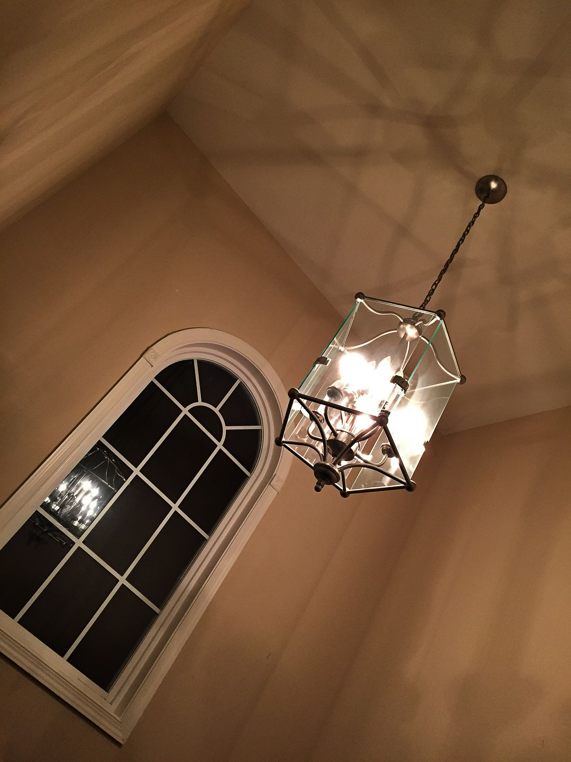 low angle view, illuminated, lighting equipment, architecture, built structure, indoors, ceiling, hanging, electricity, electric lamp, electric light, decoration, night, building exterior, no people, chandelier, light bulb, glowing, directly below, window