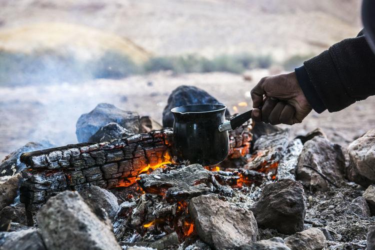 Cropped hand preparing food on wood burning stove