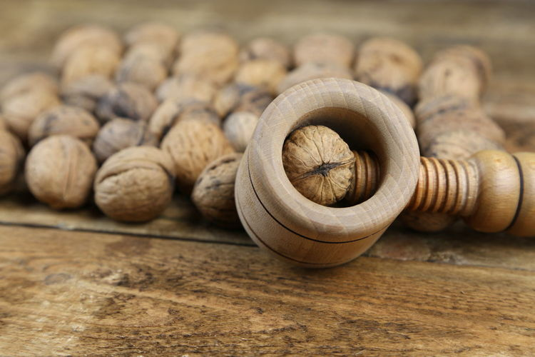 Walnuts with nutcracker on wooden table