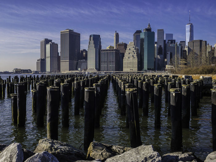 Wooden posts in sea in front of brooklyn cityscape