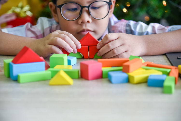 Boy playing with colorful toy blocks on table at home