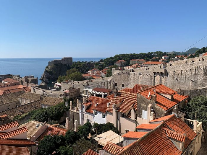 High angle view of townscape by sea against clear blue sky