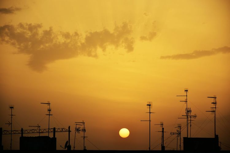 Silhouette antennas on building terrace at sunset