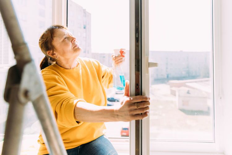 50 year old woman cleans windows from stains using rag and spray cleaner.