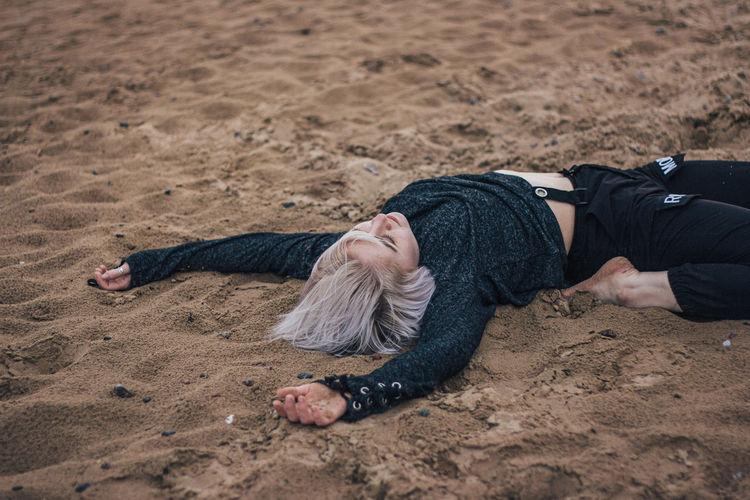 Man lying down on sand at beach