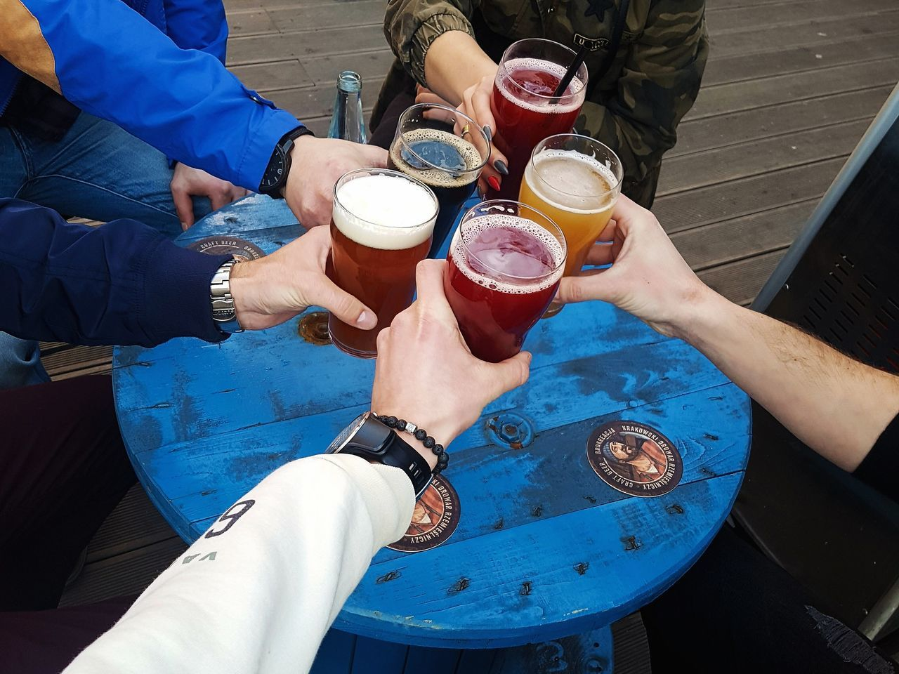 drink, beer - alcohol, alcohol, real people, food and drink, refreshment, human hand, drinking, beer glass, friendship, drinking glass, men, human body part, outdoors, beer, lifestyles, togetherness, day, leisure activity, high angle view, table, holding, women, wristwatch, water, low section, freshness, people