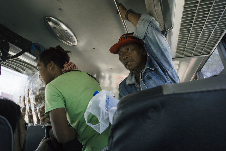Street merchants selling snacks and drinks inside a bus, Cebu City (The Philippines) ASIA Cebu Life Lifestyles Mode Of Transport People And Places Philippines Public Transportation Real People Rural Scene Street Street Life Streetphotography Tourism Travel Travel Destinations Traveling Vacations Working Working Hard