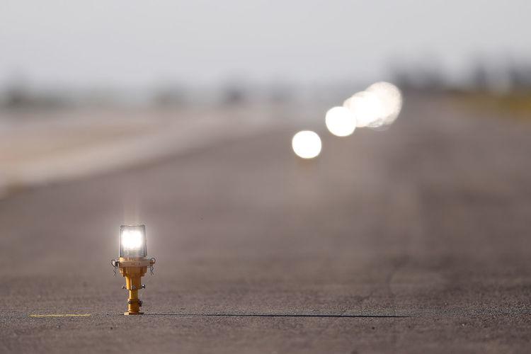 Close-up of illuminated light bulb on street against sky