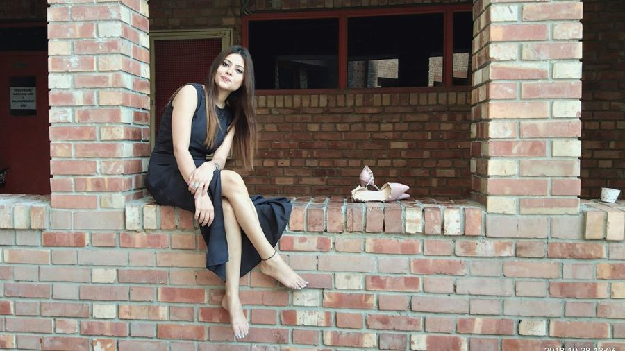 Portrait of young woman sitting on brick wall