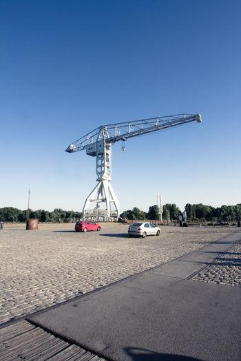 Titan crane by street against clear sky in city