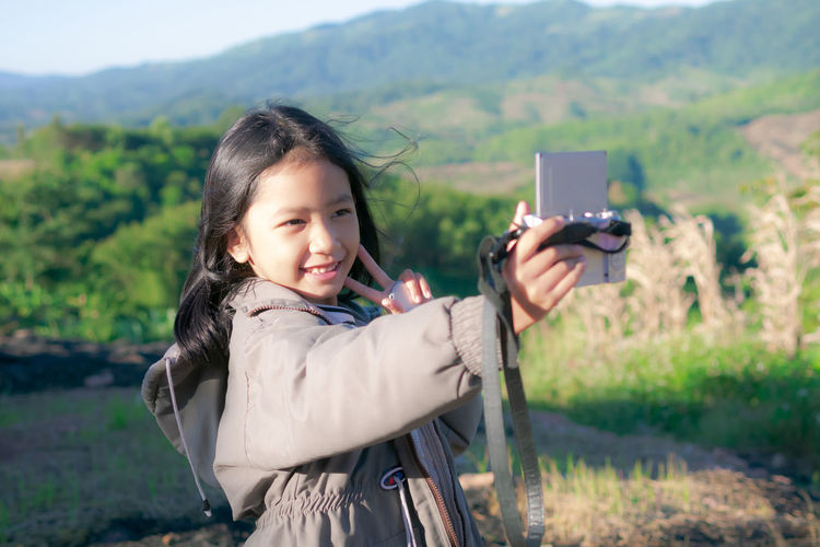 Smiling girl taking selfie with camera while standing against landscape