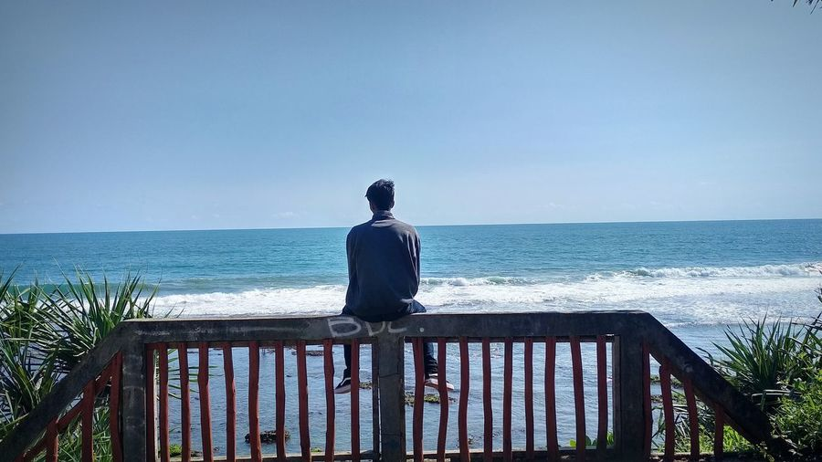 Rear view of man looking at sea while sitting on railing against sky