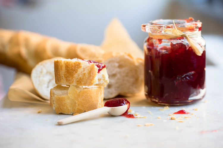 Baguette and strawberry jam on table