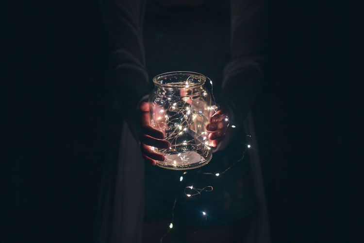 Midsection of person holding string lights in jar
