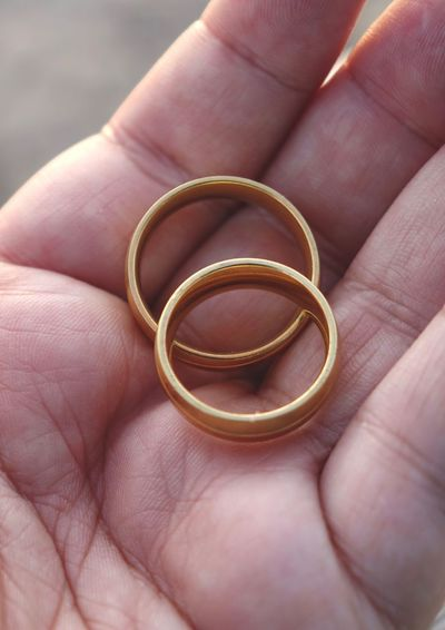 Close-up of cropped hand holding gold rings