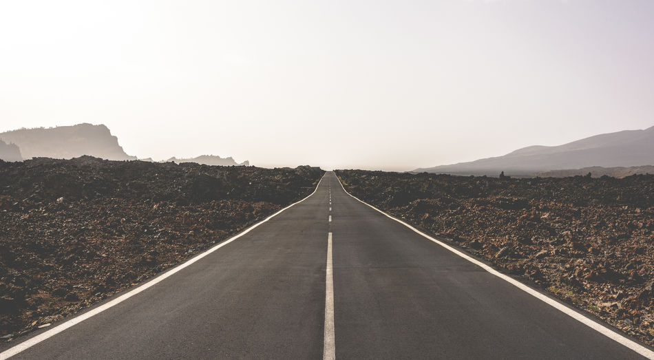 Empty road amidst field against clear sky during sunny day