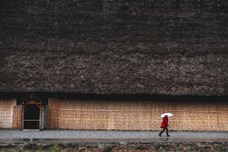 woman holding an umbrella walking on the road against old Japanese traditional house with thatched roof, Shirakawago, gifo, Japan Woman Umbrella Japanese  House Thatched Roof Shirakawago Gifo Japan Walk Road Culture Building Japan Travel Landscape Architecture Nature Wooden Village Tree Old Historic ASIA Tourism Wood Countryside Traditional Thatch Tradition Sightseeing Home Vintage Japanese  Landmark Style Folk Tatami Design Wall Ancient History Snow Decoration Buildings Tourists Farming Red Weather Journey The Minimalist - 2019 EyeEm Awards