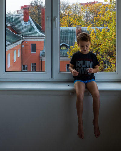 Childhood Boys Child One Person Males  Men Full Length Front View Portrait Offspring Leisure Activity Innocence Window Sitting Architecture Looking Lifestyles Shorts
