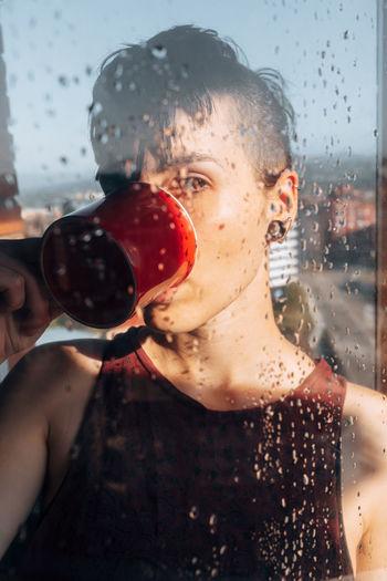 Portrait of wet man drinking glass window
