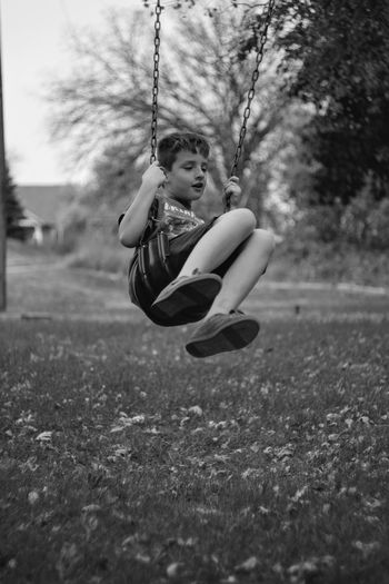 Playful boy on swing at park