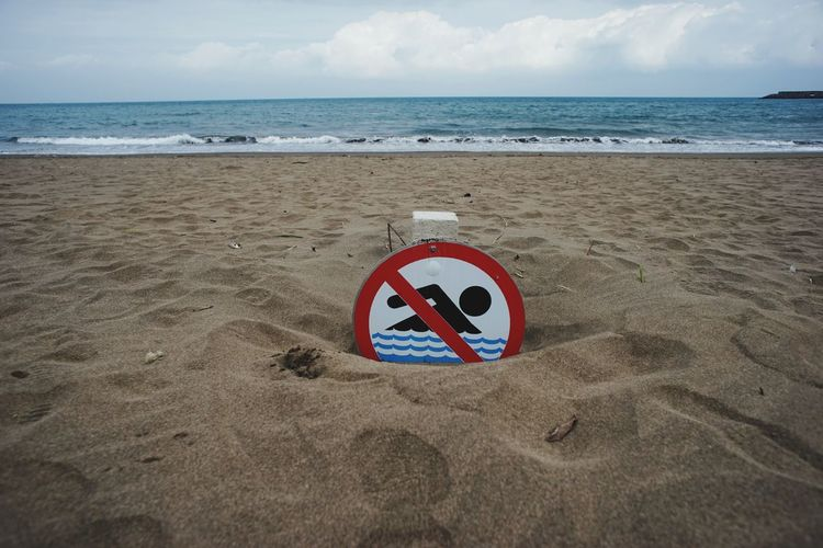 Warning sign on beach against sky