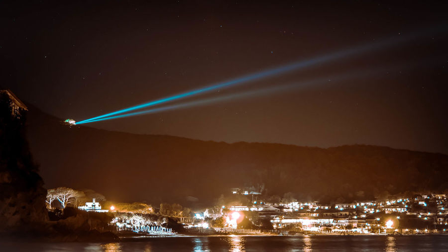Laser light by illuminated buildings and sea against sky at night