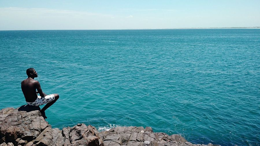 Rear view of man sitting on rock formation by sea against sky
