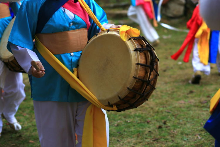 Midsection of man playing drum outdoors