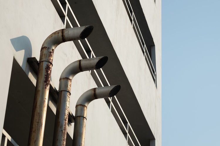 Three pipe ventilation ducts For venting smoke outside the building, rusty surface surrounding with sunlight and blue sky background. Air Exhaust Hood Tube Sunlight Low Angle View Building Exterior Metal Architecture Outdoors Sky Shadow Global Warming Smoke Kitchen Three Quarter Length Men Infrastructure HVAC System Mechanical Pink Color Pollution Greenhouse Effect Temperature Engineering Ventilation Toxic Transplant Blower Instrument Aluminium Construction Vent Heat - Temperature Chimney Funnel Rusty Service Waste Object Carbon Dioxide Equipment Design