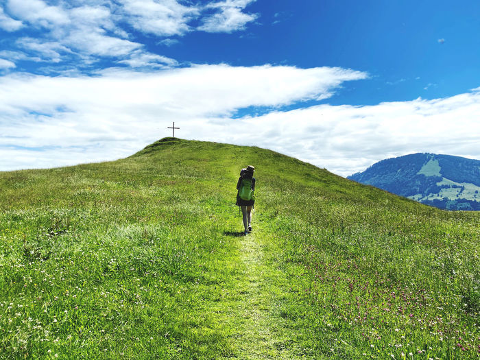 Rear view of woman walking up a grassy hill against mountains carrying child and backpack