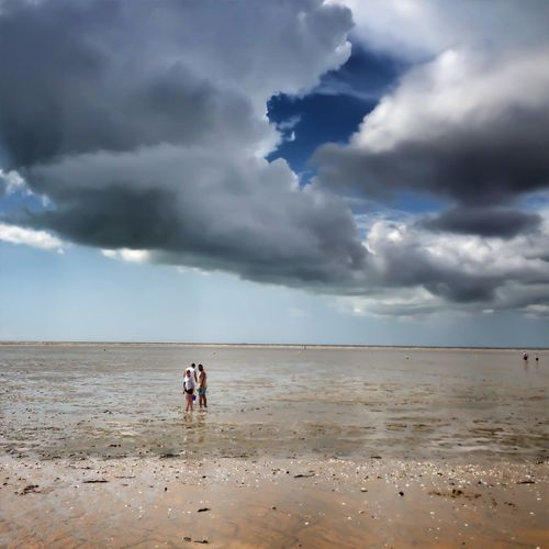 People on shallow beach against cloudy sky