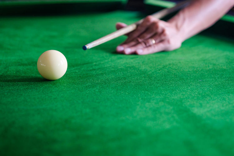 Cropped hand of man playing pool ball