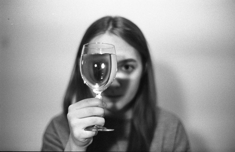 Portrait of woman holding glass against wall