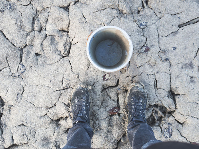 Low section of man standing by empty bucket on cracked landscape