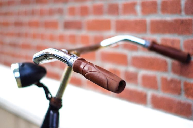 Close-up of bicycle against brick wall