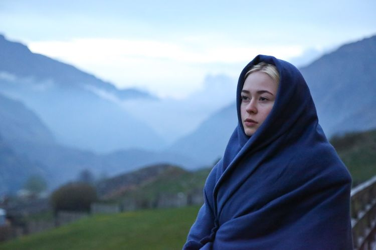 Beautiful woman wrapped in blanket standing on mountain against sky
