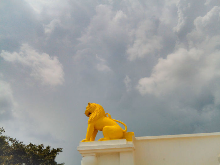 Low angle yellow of lion statue on building against sky
