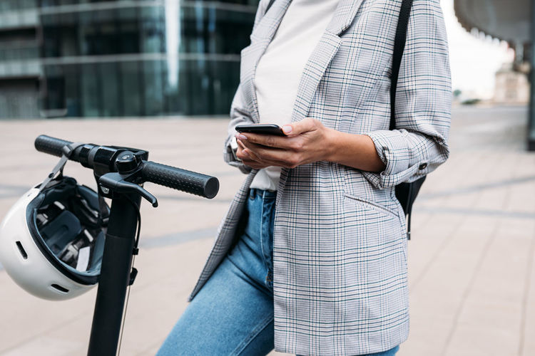 Cropped shot of female in casuals using an app on a cell phone for unlocking electric push scooter