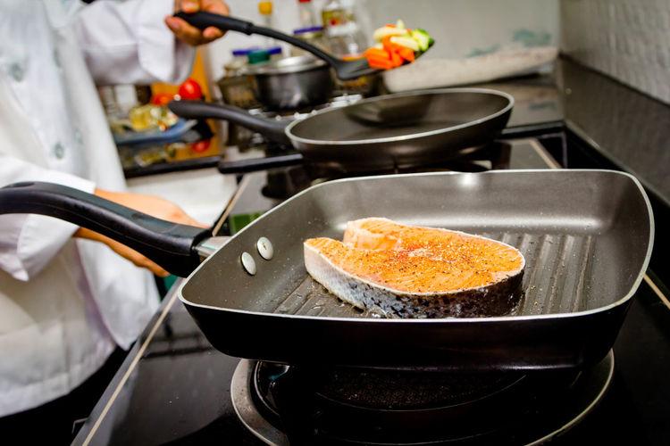 Chef making fresh salmon steak on wooden board