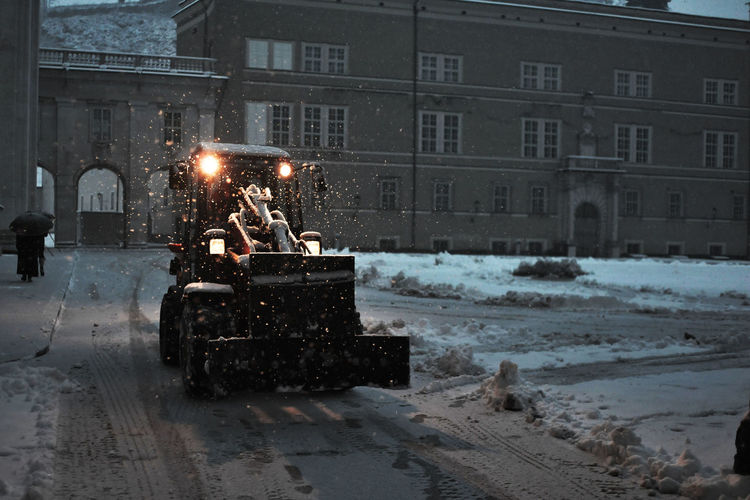 Earth Mover On Snowcapped Road In City At Dusk