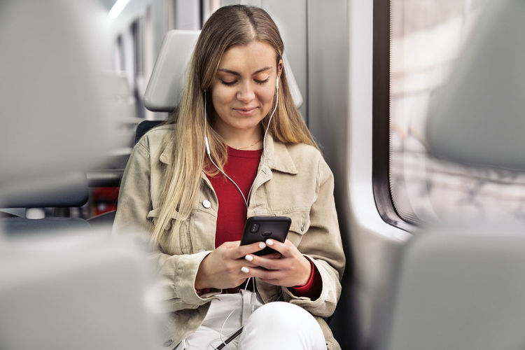 Young woman using mobile phone while sitting in bus