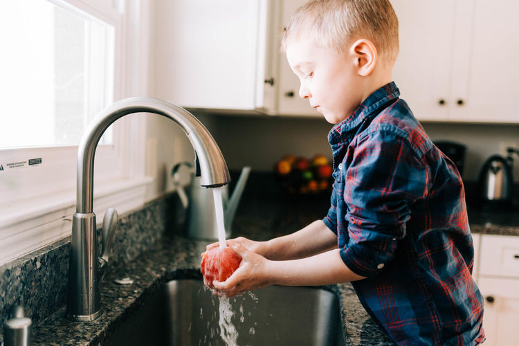 Close-up of boy with faucet in water at home
