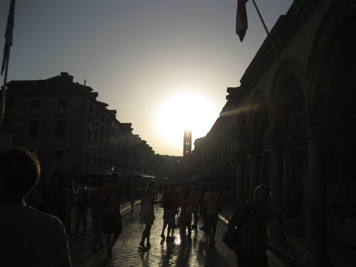 People walking in city at sunset